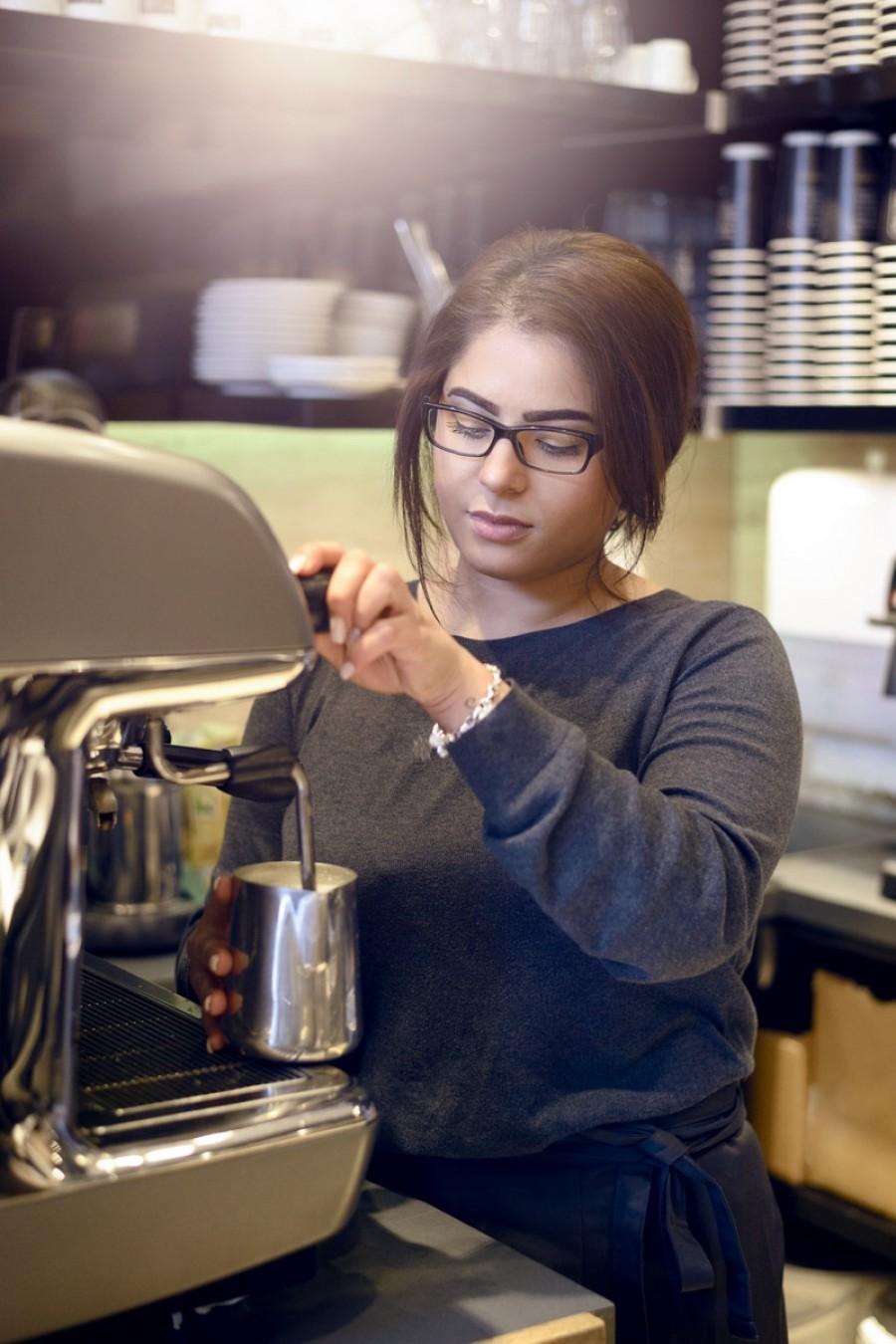 A young barista makes a coffee